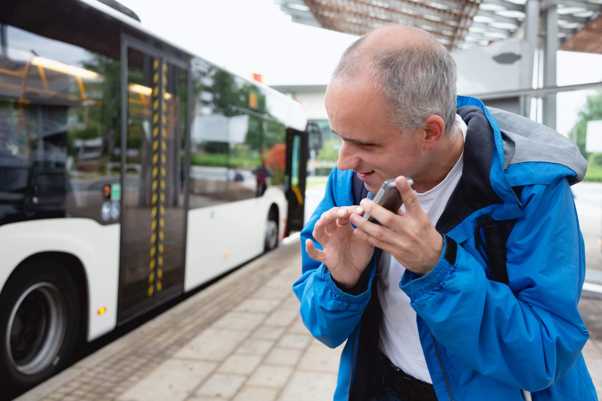 Blind man listening to his smartphone at a bus station