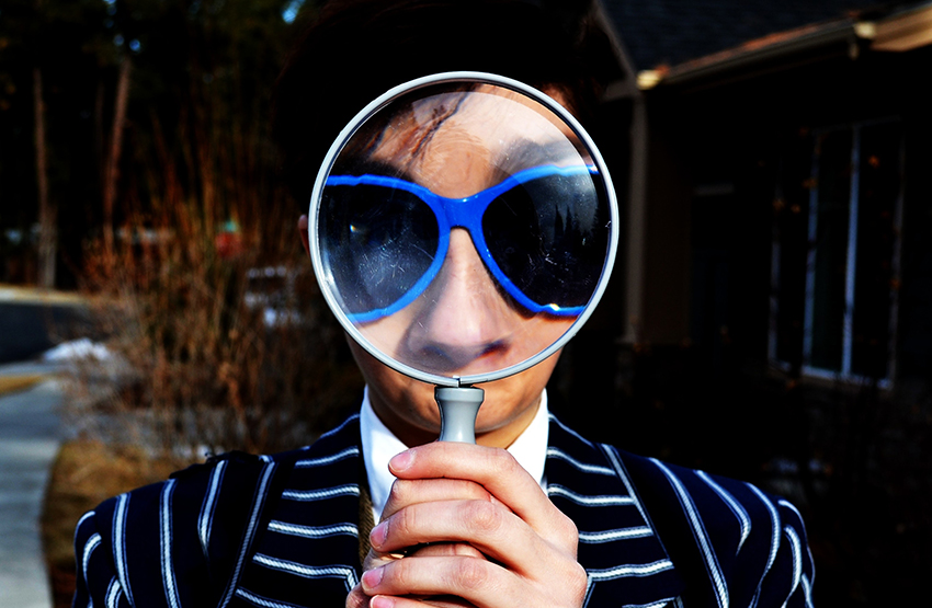 Person with a magnifying glass before his face