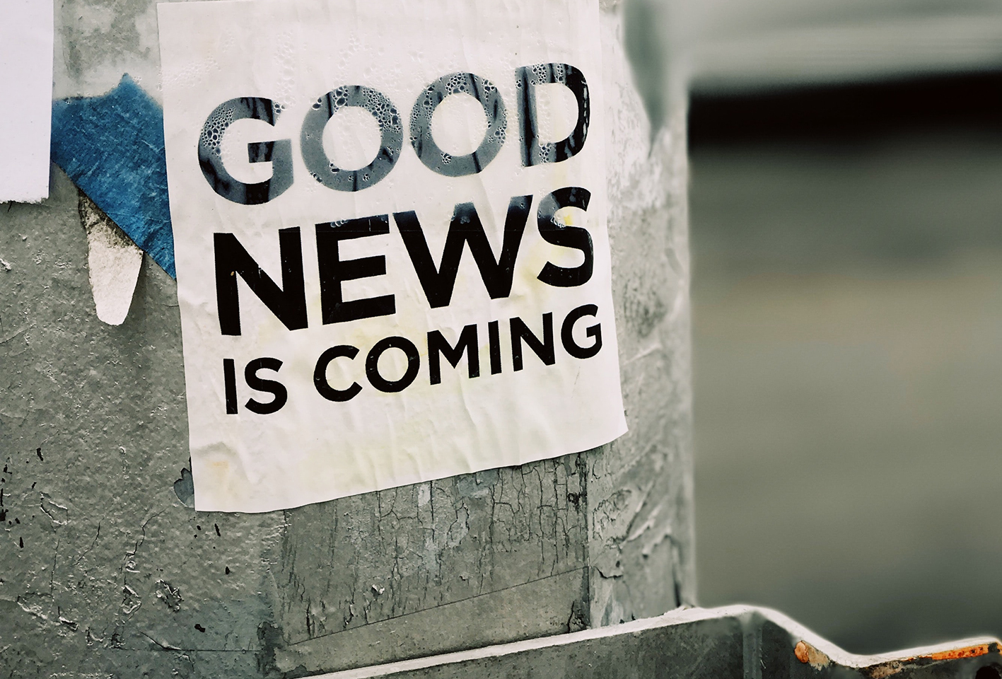 Poster on pole in street saying Good News is Coming