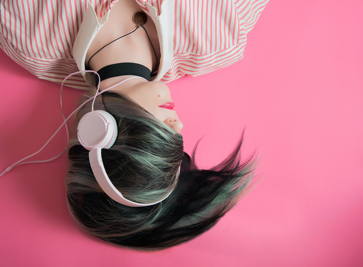 woman lying down with headphones and her hear covering her eyes