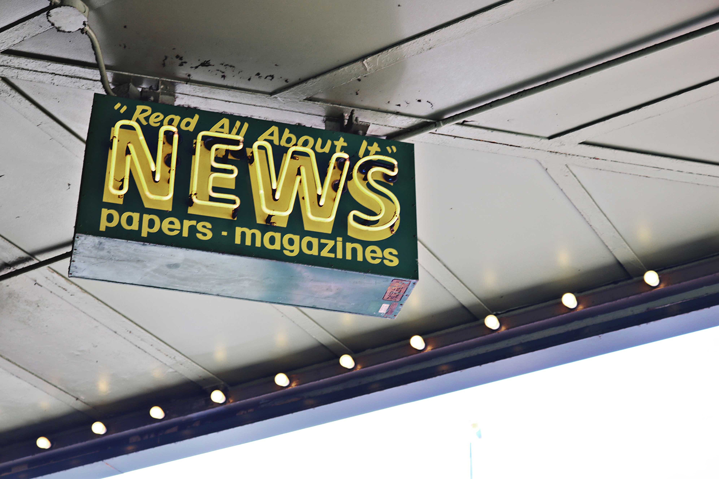 Advertisement sign under a roof saying News Read All About It