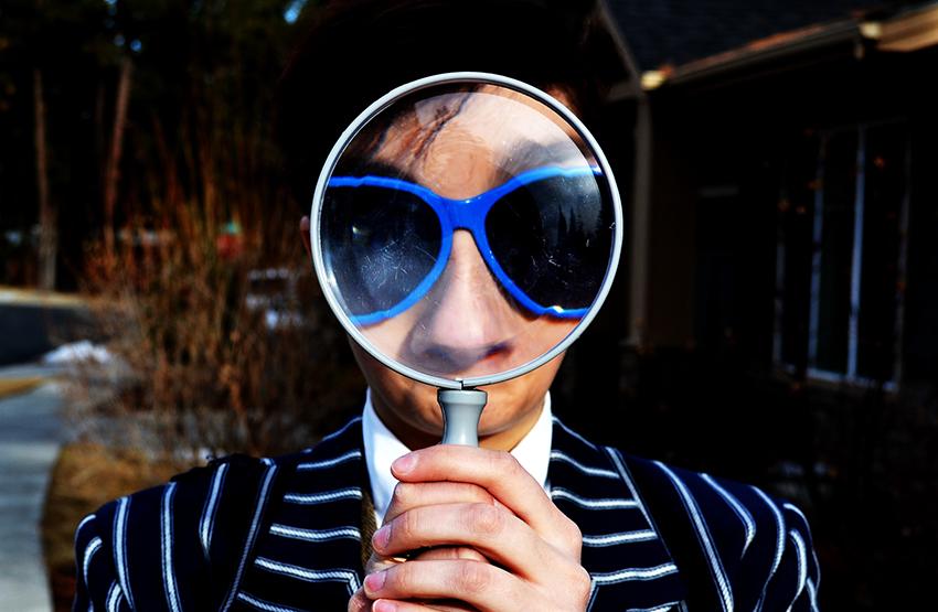 Iemand met vergrootglas voor gezicht