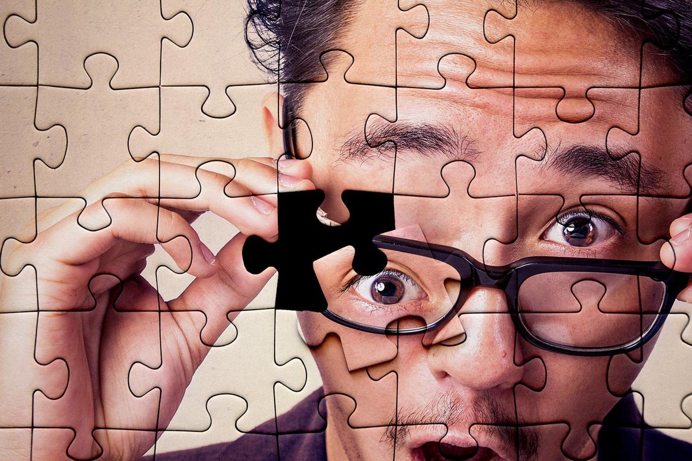 Legpuzzel van verbaasde man waarbij het laatste stukje van zijn oog los op de puzzel ligt