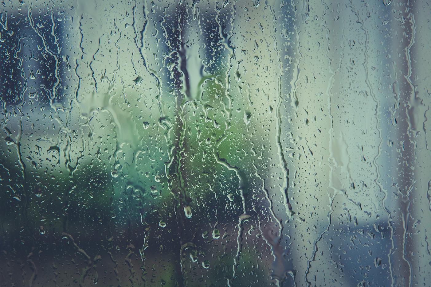 UItzicht naar buiten door met regendruppels beslagen raam
