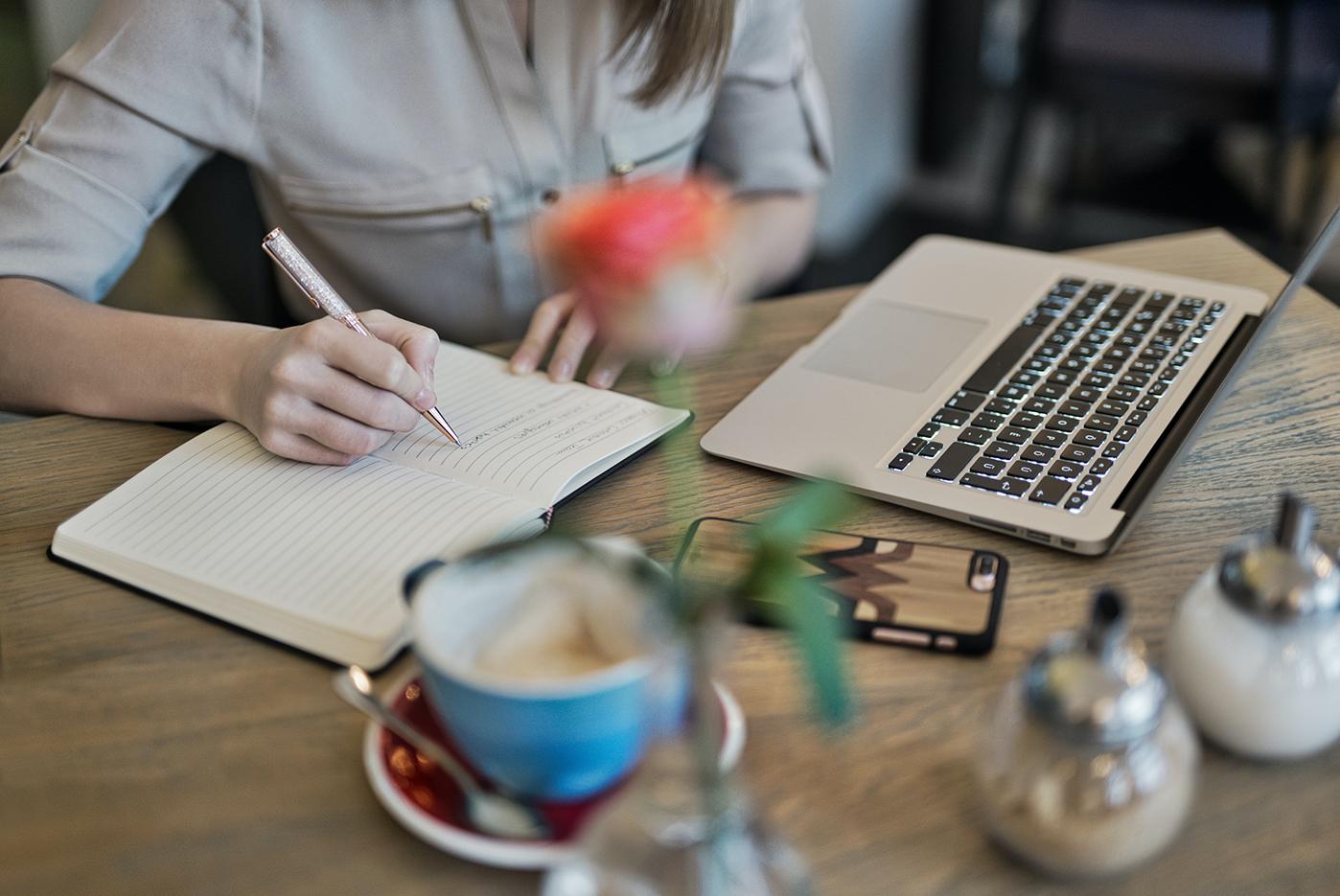 Iemand die notities maakt naast een laptop