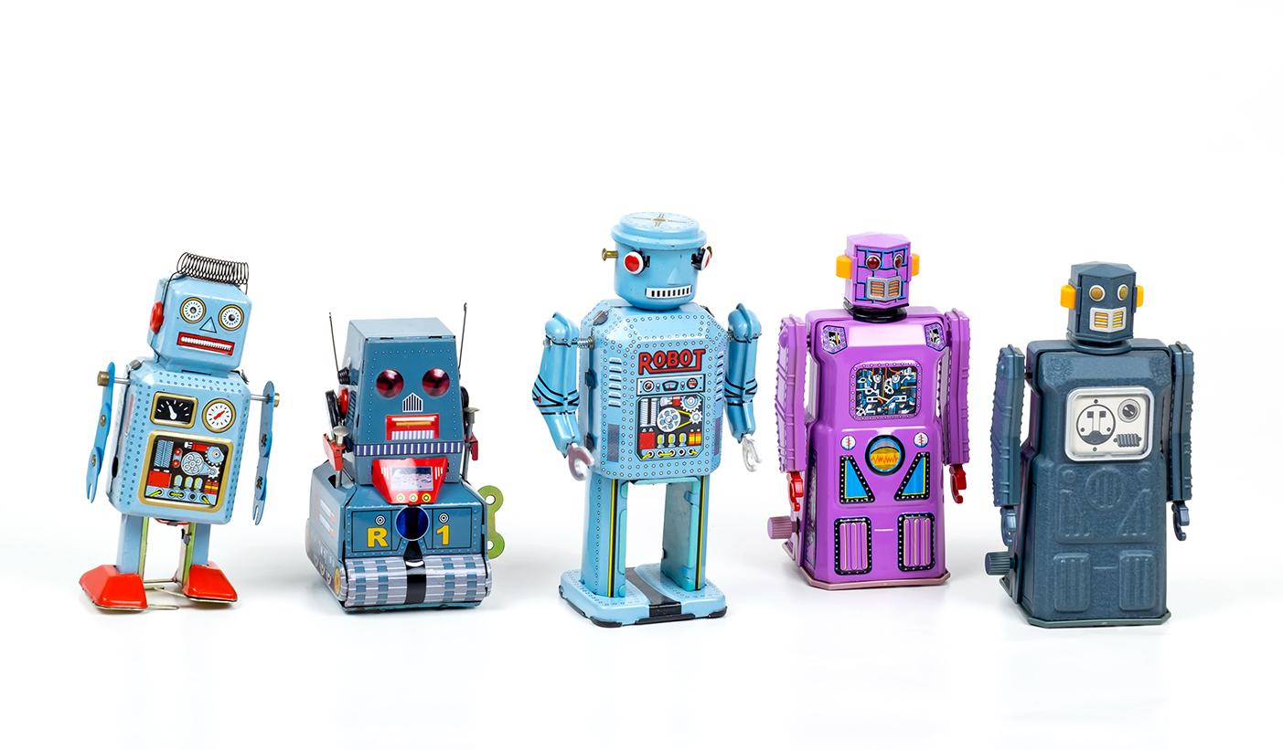 Vijf speelgoed robotjes op een rij