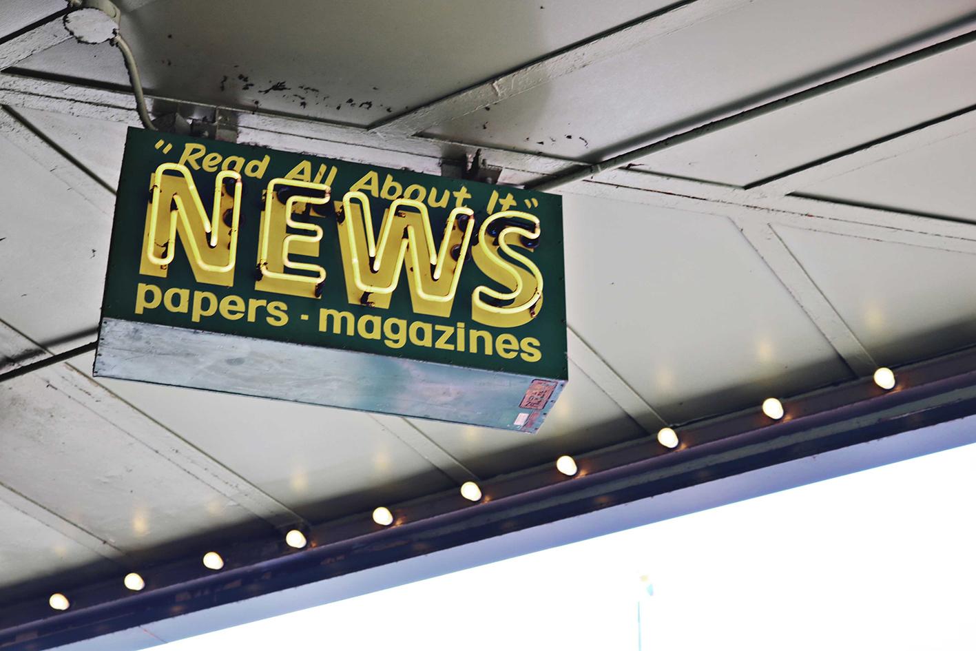 Reclamebord hangend aan dak met tekst News Read All About It