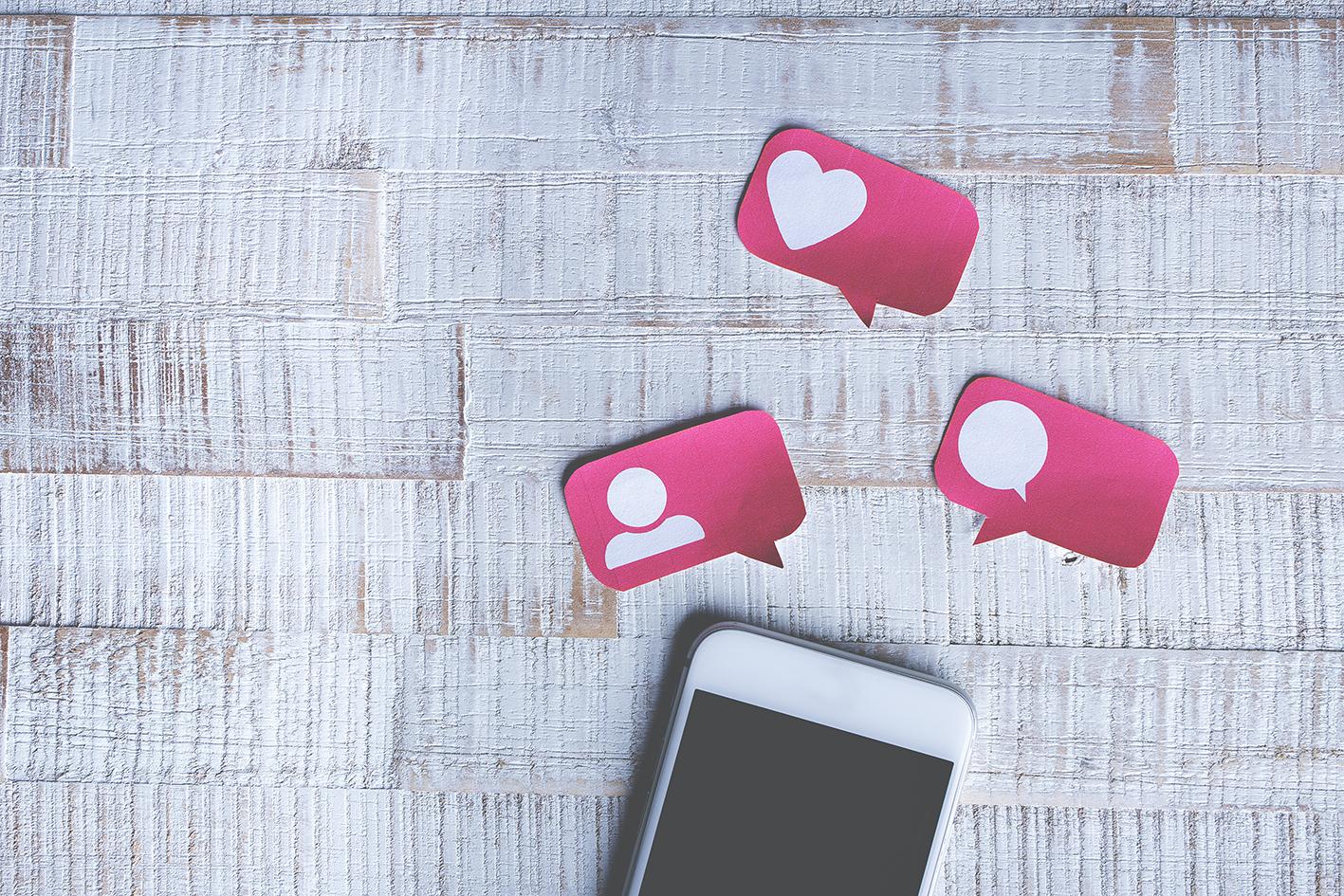 Smartphone met daarboven uitgeknipte tekstbalonnetjes met social media symbolen